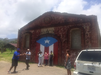 """Historic Maunabo warehouse with one of the 78 flags artist """"Hector"""" was painting across the island"""